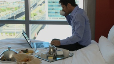 LS OF A BUSINESSMAN WORKING IN HIS HOTEL ROOM