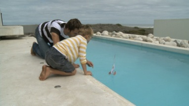 LS OF A FATHER AND SON PLAYING WITH A TOY BOAT