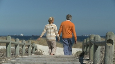 LS OF A SENIOR COUPLE WALKING TO THE BEACH