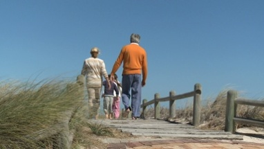 LS REAR VIEW OF GRANDPARENTS WALKING WITH THEIR GRANDCHILDREN TO THE BEACH