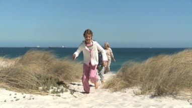 LS OF GRANDCHILDREN RUNNING IN FRONT OF THEIR GRANDPARENTS ON THE BEACH