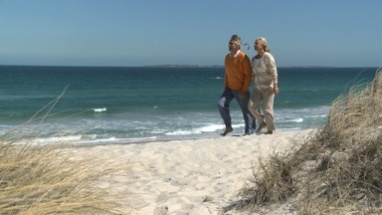 LS PAN OF A SENIOR COUPLE WALKING ALONG A BEACH