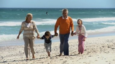 LS OF GRANDPARENTS AND THEIR GRANDCHILDREN WALKING ALONG THE BEACH
