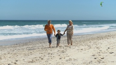 LS PAN OF GRANDPARENTS WALKING ALONG THE BEACH WITH THEIR GRANDSON