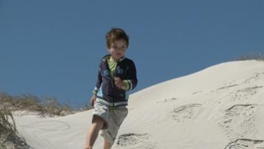LS PAN OF A BOY RUNNING DOWN A SAND DUNE
