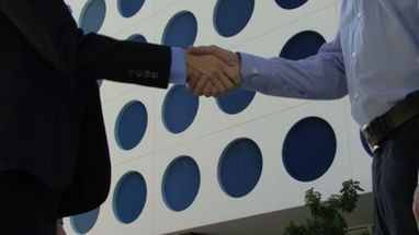 Cu of male and female greeting with handshake