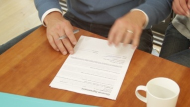 Close up off couple signing contract at dinning table