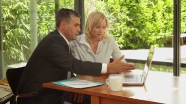 Wide, shot off female at dinning table with financial advisor showing documents on laptop