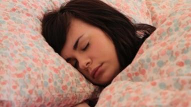 Female sleeping in bed under duvet