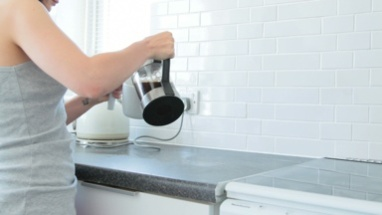 Person pouring coffee from french press into cup