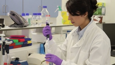Female Scientist in science laboratory and looks at screen with stem cells