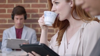 CU TU Woman using tablet and drinking coffee in coffee shop / London, Greater London, United Kingdom.