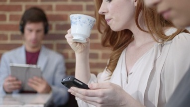 CU TU Woman using mobile phone and drinking coffee in coffee shop / London, Greater London, United Kingdom.
