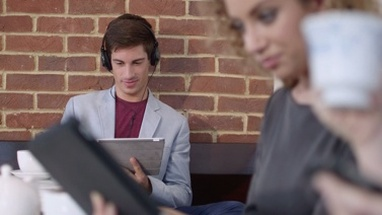 MS Man listening music while woman using digital tablet in coffee shop / London, Greater London, United Kingdom.