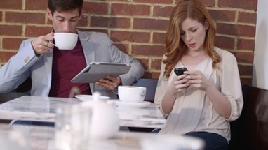 MS TU Couple using mobile phone and digital tablet in cafe / London, Greater London, United Kingdom.