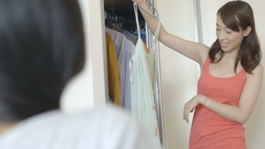 MS TU Young woman trying clothes near cupboard