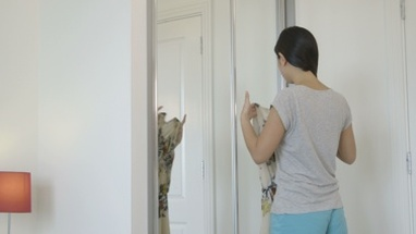 MS Young woman trying clothes near mirror