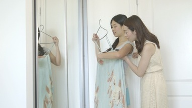 MS Young woman trying clothes near mirror and talking with friend