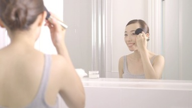 MS PAN Young woman applying make-up in front of mirror