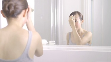 MS FI Young woman applying make-up in front of mirror