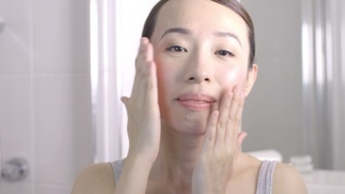 CU Young woman massaging her face and smiling