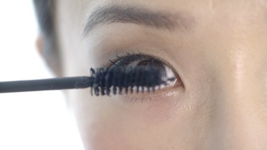 CU Young woman applying black mascara