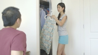 MS Young woman showing dress to man in bedroom