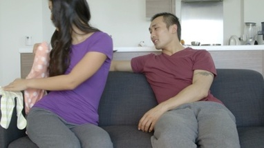 MS Asian young woman showing at baby clothes to man in living room