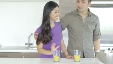 MS Young couple standing and drinking juice in kitchen