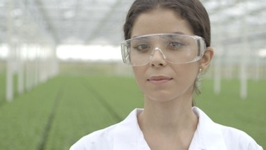 CU Scientist wearing safety glasses in a greenhouse