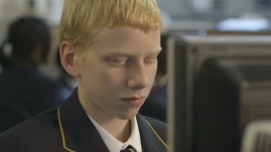 CU TU Schoolboy using computer in computer laboratory