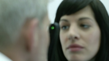 Female Optician uses a Ophthalmoscope to closely examine the eyes of the Male Patient