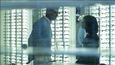 Female Optician guides and asssits Male patient to choose a new pair of glasses