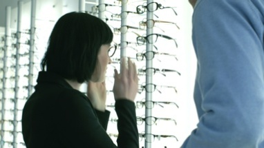 Female patient tries on glasses with the assistance of the Male of Optician
