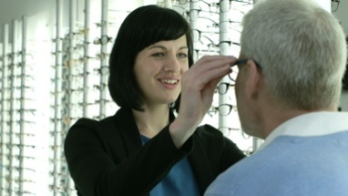 Female Optician offers the Male patient a pair of glasses to try on