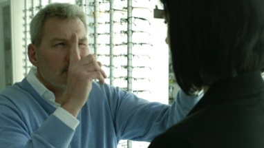 Male Optician places Optical Ruler on the nose of the Female patient to assess the best suitable lenses for her.