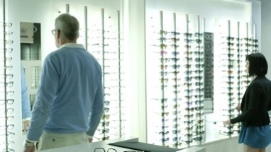 Male and Female Customers browse the optician shop, looking at the glasses on display.