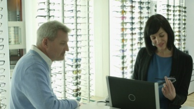 Male Patient purchases a new pair of glasses with the assistance of the Female Optician