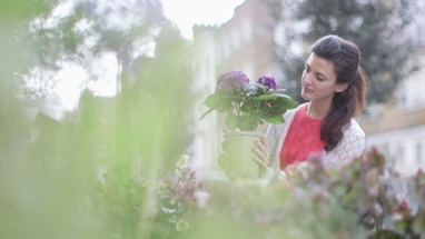 Young woman browses an array of flowers outside a Florist and picks up to inspect