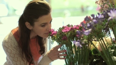 Young woman browses an array of flowers inside a Florist and smells them eagerly