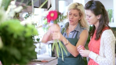 A Florist demonstrates how to create an effect bouquet to an eager learning Apprentice