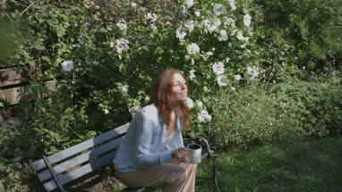 Woman sitting on bench and drinking coffee in garden