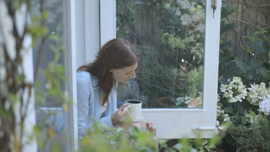 Woman stroking cat while drinking coffee outside home
