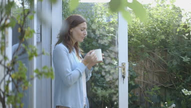 Woman drinking coffee outside home