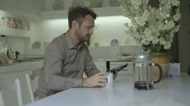 Man using digital tablet while drinking coffee