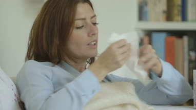 Woman covered in blanket, wiping her nose due to cold