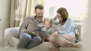 Parents showing digital tablet to their daughter at home