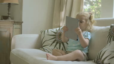 Baby girl curiously looking at digital tablet