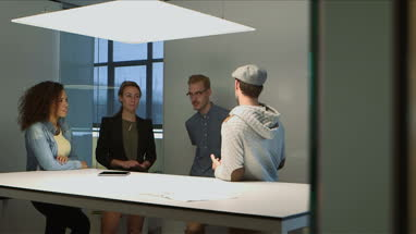 Four architects discussing with blueprint and tablet