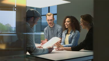 Four business people discussing with document